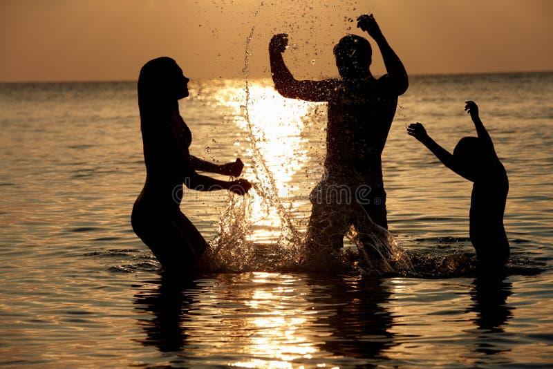 Silhouet van Familie die Pret in Overzees op Strandvakantie hebben stock fotografie