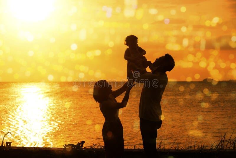 Silhouet van familie in openluchtstrandzonsondergang royalty-vrije stock afbeelding