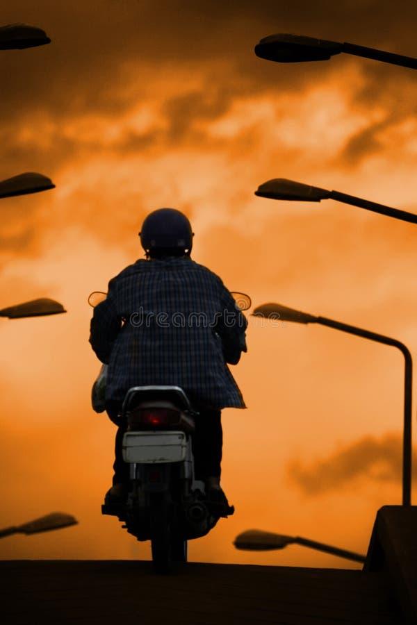 Silhouet van fietser berijdende motorfiets op de brug royalty-vrije stock foto's