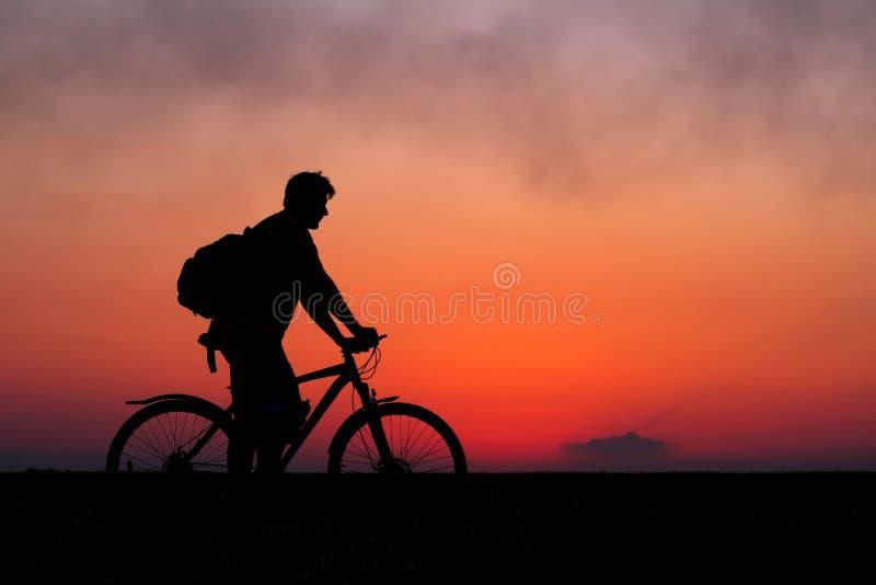 Silhouet van fietser op de achtergrond van rode zonsondergang Fietserverstand royalty-vrije stock foto
