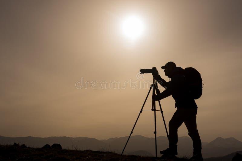 Silhouet van fotograaf bij zonsondergang stock fotografie