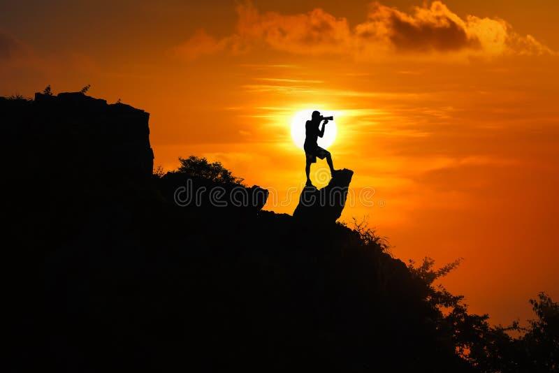 Silhouet van fotograaf bovenop berg bij zonsondergang rode hemel royalty-vrije stock foto's