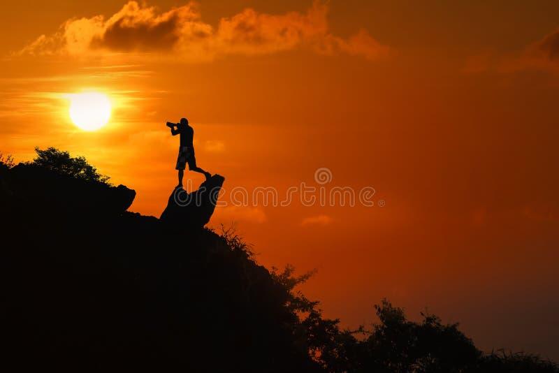 Silhouet van fotograaf bovenop berg bij zonsondergang rode hemel royalty-vrije stock fotografie