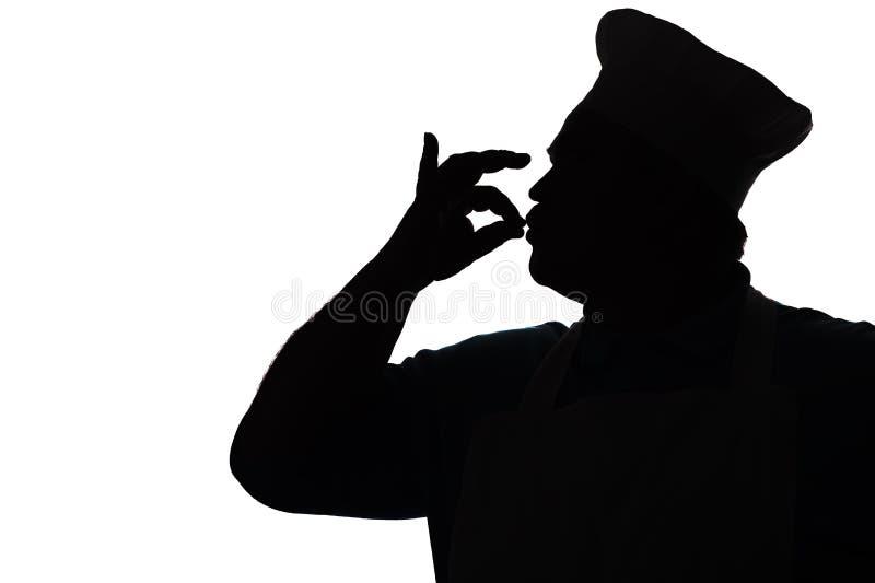 Silhouet van gelukkige chef-kok het kussen vingers uit heerlijke schotels, het profiel van een persoon in een keuken eenvormig to royalty-vrije stock afbeeldingen