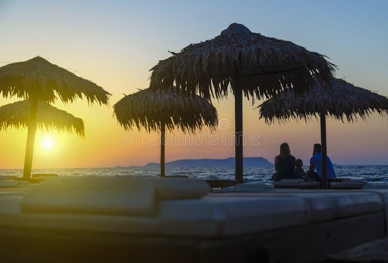 Silhouet van gelukkige mensen dat het letten op zonsondergangtijd op het strand Zij die pret op de aard hebben Concept gelukkig royalty-vrije stock foto's