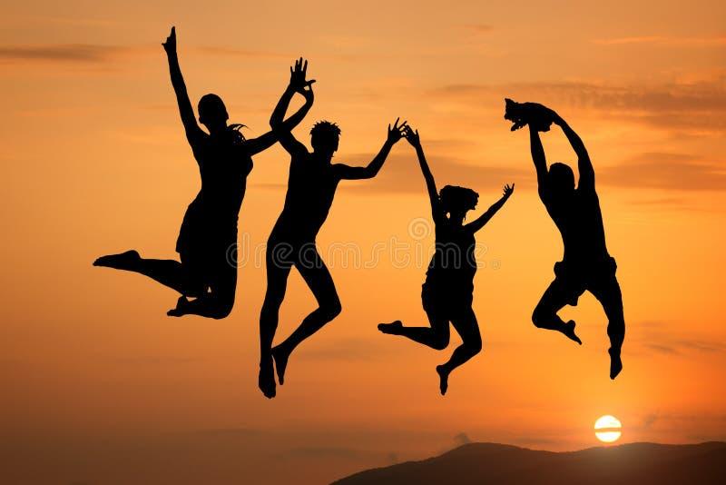 Silhouet van gelukkige mensen die bij zonsondergang springen stock fotografie