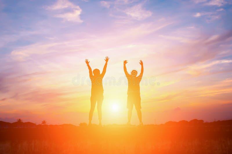 Silhouet van gelukkige mensen die hoge handen maken stock fotografie