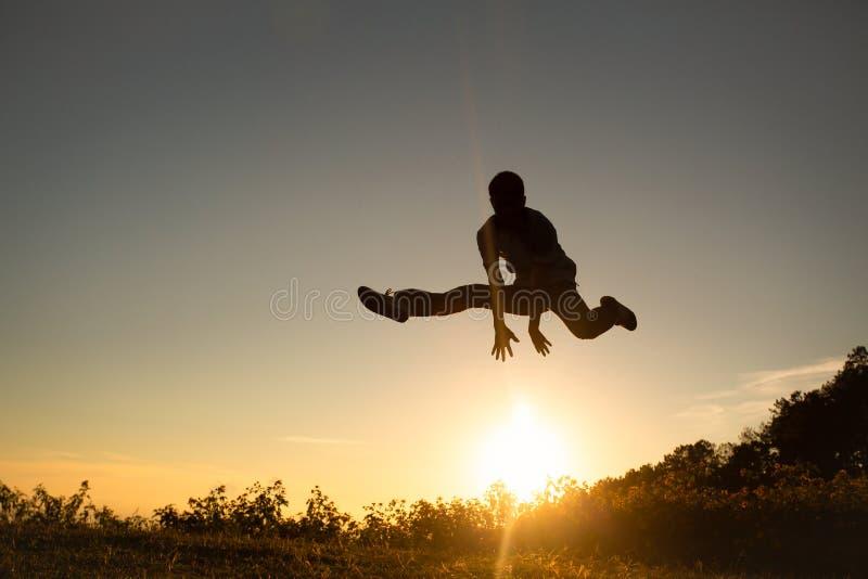 Silhouet van gelukkige mensen die in zonsondergang op Moutain springen stock foto's