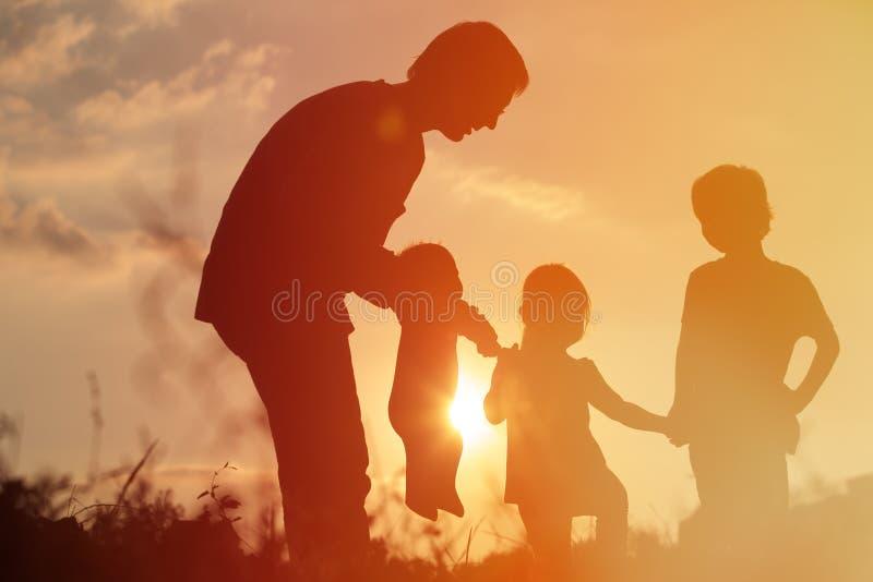 Silhouet van gelukkige vader met boomjonge geitjes bij zonsonderganghemel stock foto