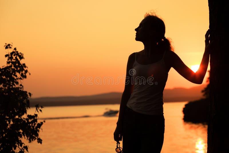 Silhouet van gelukkige vrouw die die zich op de kust van meer bevinden stock foto's