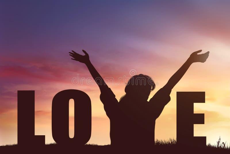 Silhouet van gelukkige vrouw met Liefdetekst bij zonsondergang royalty-vrije stock foto