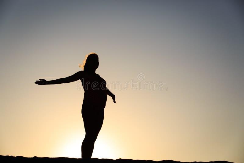 Silhouet van gelukkige zwangere vrouw bij zonsondergang stock fotografie