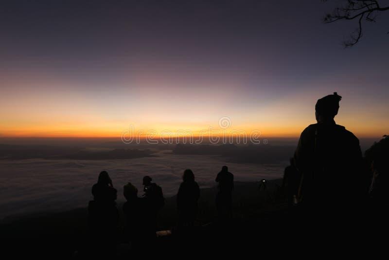 Silhouet van groep reizigers die van een mooie zonsopgang genieten stock foto