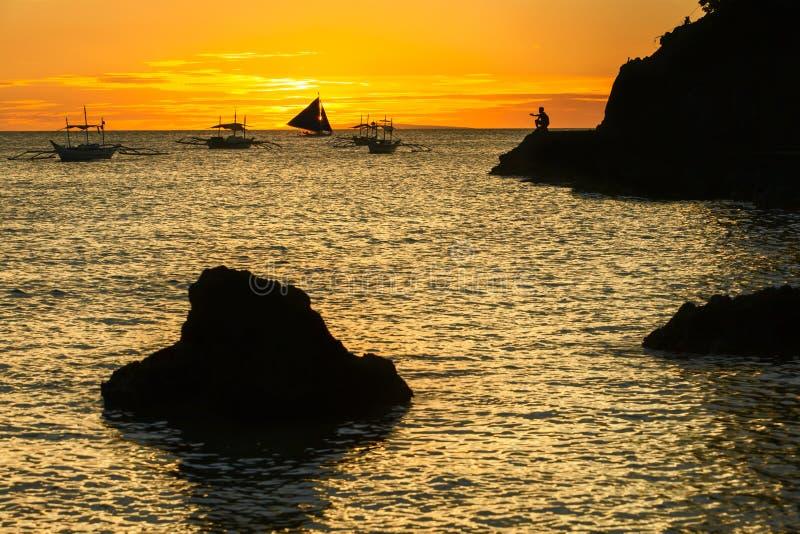 Silhouet van grote zwarte steen en varend boot en tropische eiland op zonsondergang Filippijnen royalty-vrije stock afbeelding