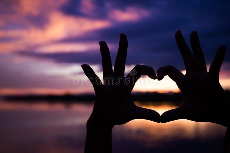 Silhouet van handen met hartvorm met mooie kleurenzonsondergang royalty-vrije stock afbeelding