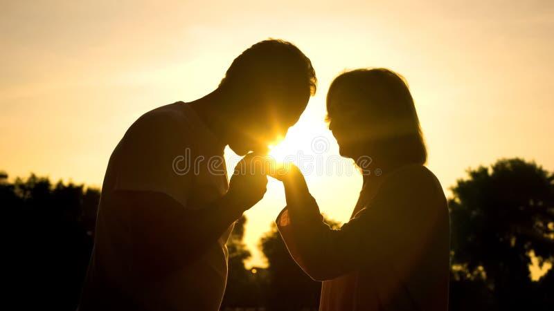 Silhouet van heer het kussen de hand van de vrouw, hoger paar in Romaanse liefde, stock foto