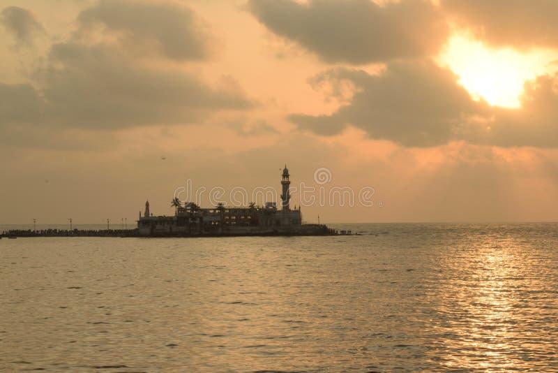 Silhouet van het Beroemde Haji Ali-graf op de Arabische die zeekust tegen een hemelpatroon door wolken en de het plaatsen zon wor stock fotografie