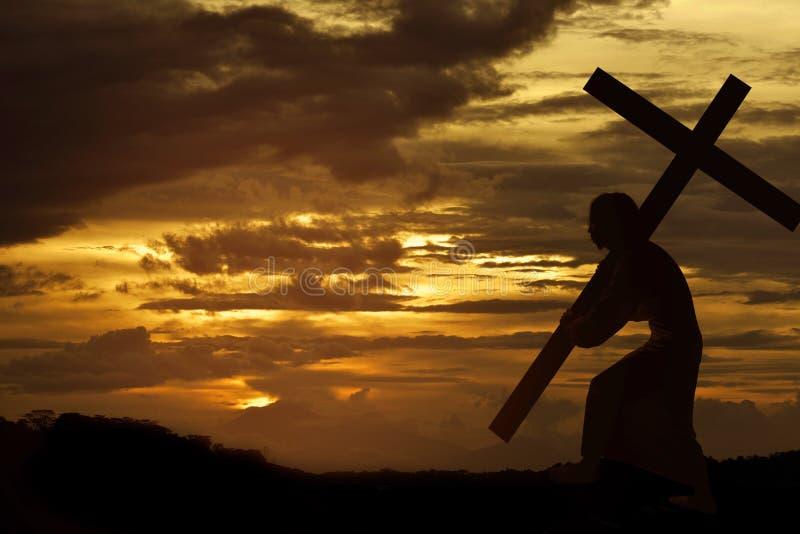 Silhouet van het dragende kruis van Jesus-Christus stock afbeelding