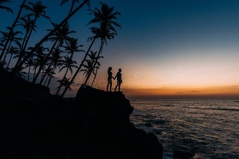 Silhouet van het houden van van paar op overzees Man en vrouw bij zonsondergang r E Het gelukkige houden van stock foto's