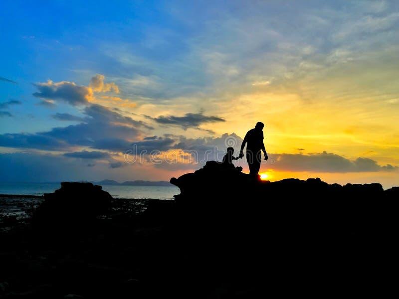Silhouet van het houden van van vader en zoon op kust en beauti wordt gelopen die royalty-vrije stock fotografie
