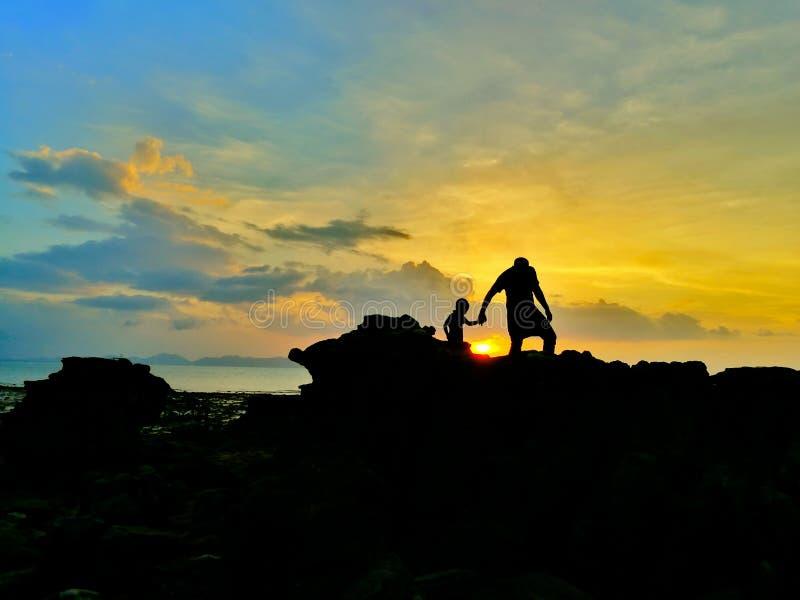 Silhouet van het houden van van vader en zoon op kust en beauti wordt gelopen die royalty-vrije stock afbeeldingen