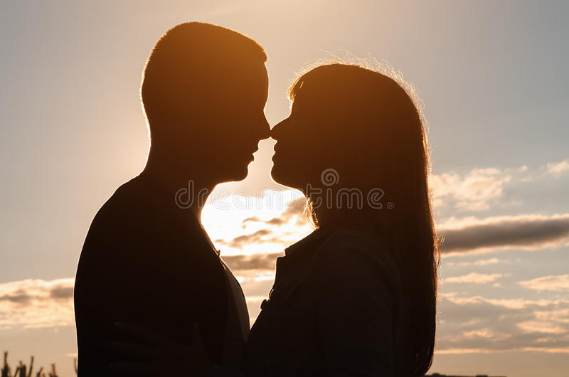 Silhouet van het houden van van paar die bij zonsondergang omhelzen royalty-vrije stock foto's