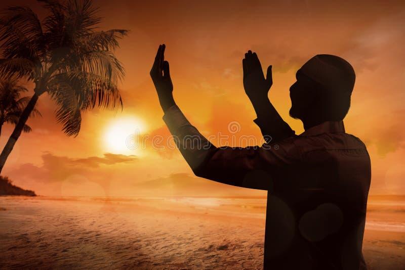 Silhouet van het jonge moslimmens bidden stock foto's