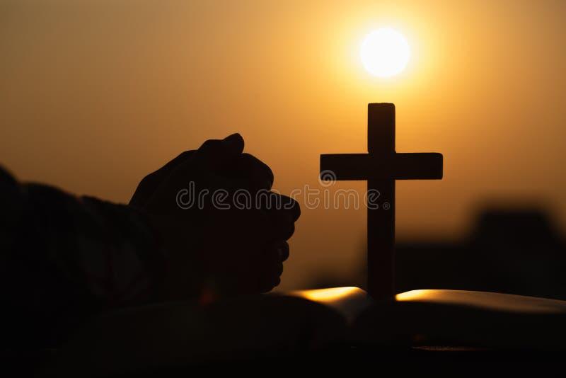 Silhouet van het jonge vrouw bidden met kruisen en bijbels bij zonsopgang, Christian Religion-conceptenachtergrond royalty-vrije stock foto
