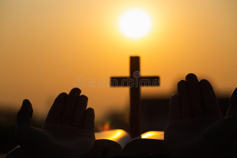 Silhouet van het jonge vrouw bidden met kruisen en bijbels bij zonsopgang, Christian Religion-conceptenachtergrond stock afbeelding