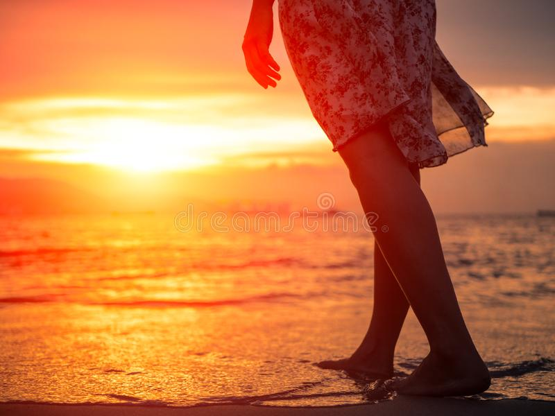 Silhouet van het Jonge vrouw lopen alleen op het strand in de zonsondergang stock afbeelding