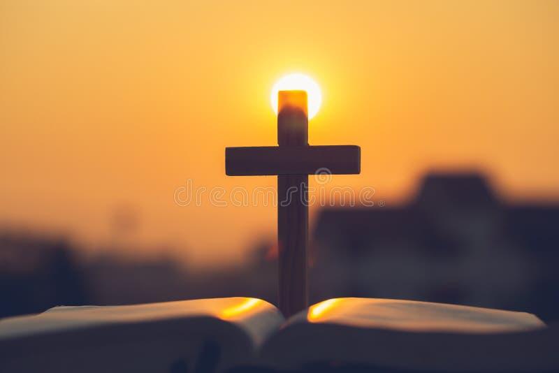 Silhouet van het kruis op de heilige bijbel, godsdienstsymbool in licht en landschap over een zonsopgang, godsdienstige achtergro stock afbeeldingen