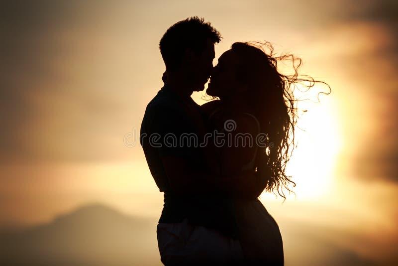 silhouet van het kussen van kerel en meisje bij dageraad stock foto's
