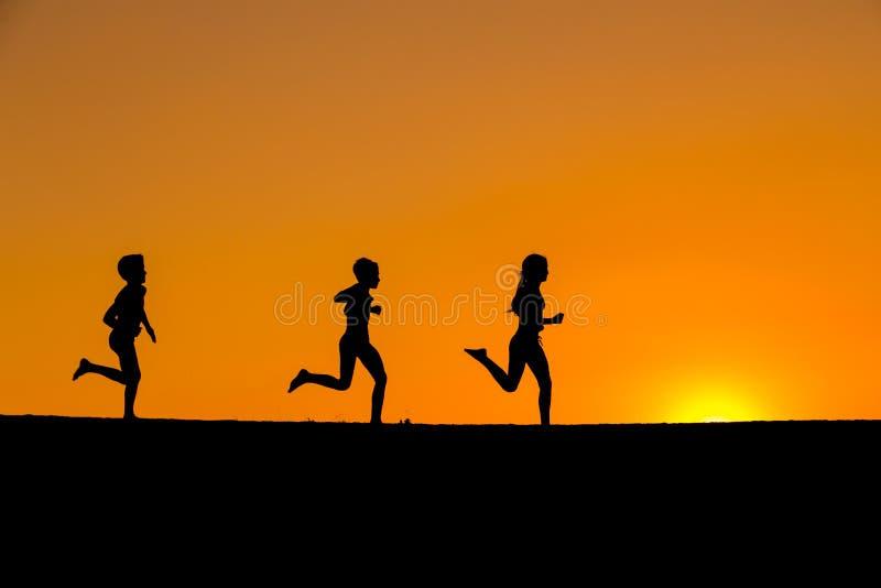 Silhouet van het lopen jonge geitjes tegen zonsondergang royalty-vrije stock foto