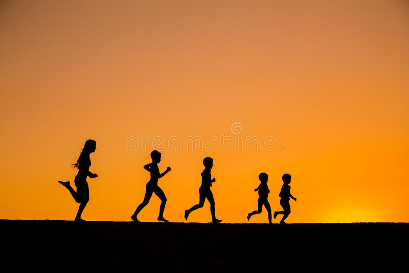Silhouet van het lopen jonge geitjes tegen zonsondergang royalty-vrije stock fotografie
