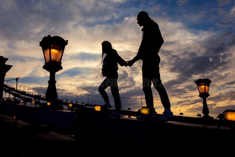 Silhouet van het lopende paar door de hand langs het hoogtepunt van de Kettingsbrug van bliksemstraatlantaarns in Boedapest, Hong stock foto