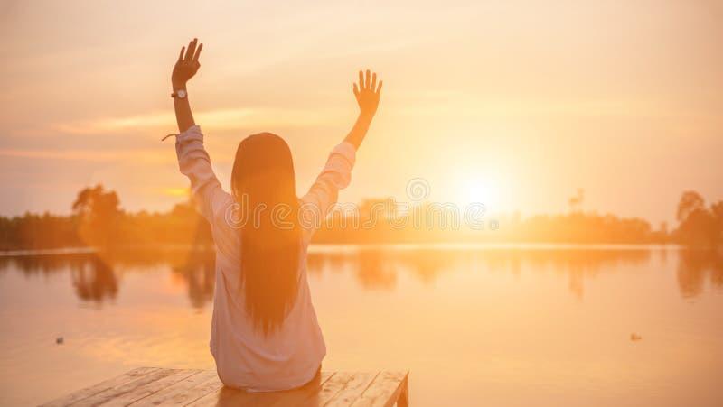 Silhouet van het mooie meisje in de aard bij de zomerzonsondergang royalty-vrije stock afbeeldingen
