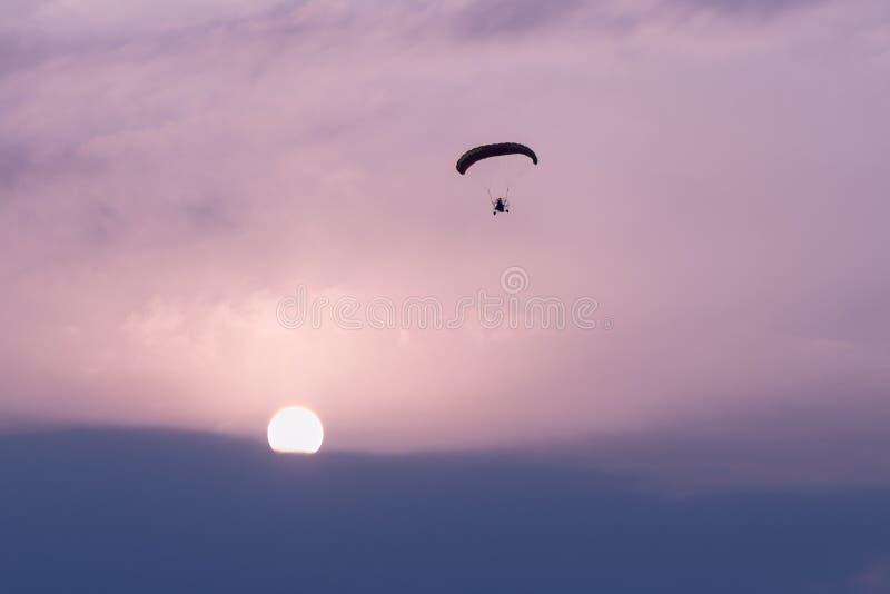 Silhouet van het proef vliegen bij zonsopgang op een gemotoriseerd valscherm bij een festival van de hete luchtballon royalty-vrije stock afbeeldingen