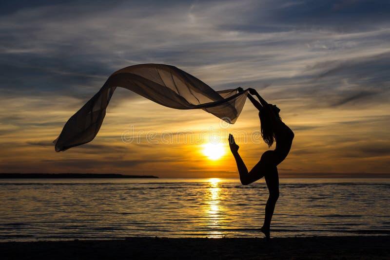 Silhouet van het slanke sexy meisje dansen met sjaal op het strand royalty-vrije stock afbeeldingen