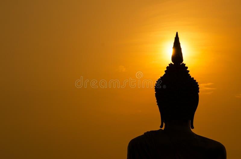 Silhouet van het standbeeld van Boedha in zonsondergang stock foto