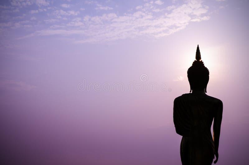 Silhouet van het standbeeld van Boedha in zonsondergang stock afbeelding