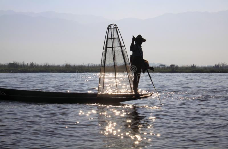 Silhouet van het traditionele visser in evenwicht brengen op zijn boot en het roeien met zijn voer op Inle-Meer, Myanmar royalty-vrije stock foto
