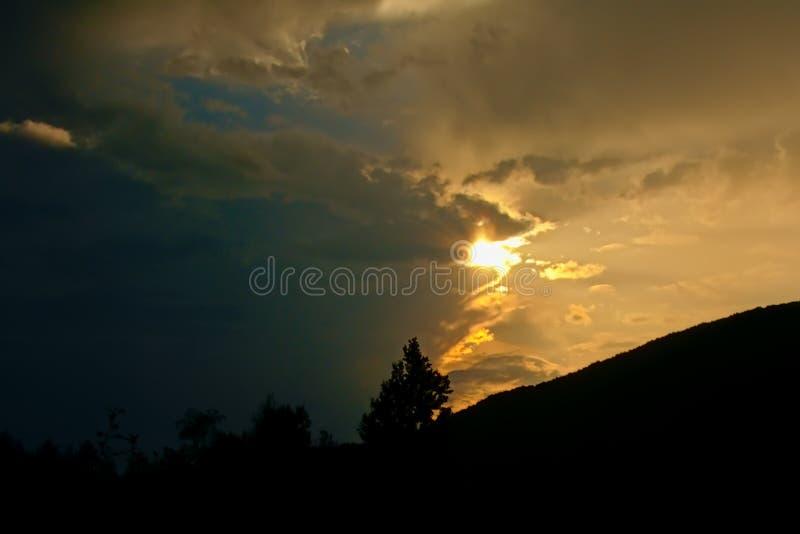 Silhouet van heuvelhelling met bomen onder een bewolkte zonsondergang stock afbeeldingen