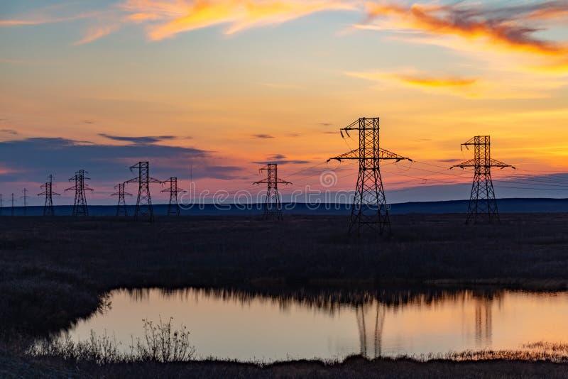 Silhouet van hoogspanningsposten bij zonsondergang Norilsk stock afbeelding