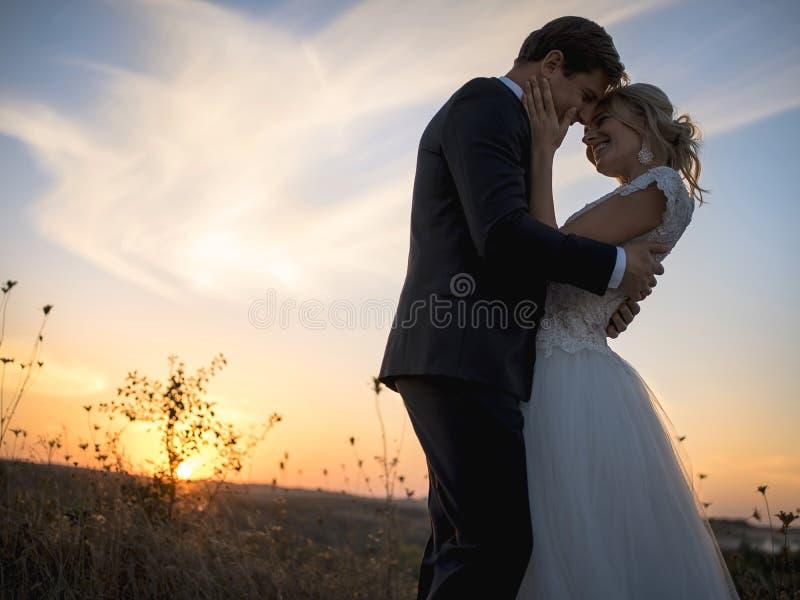 Silhouet van huwelijkspaar in liefde Tegen de het plaatsen zon binnen royalty-vrije stock foto's