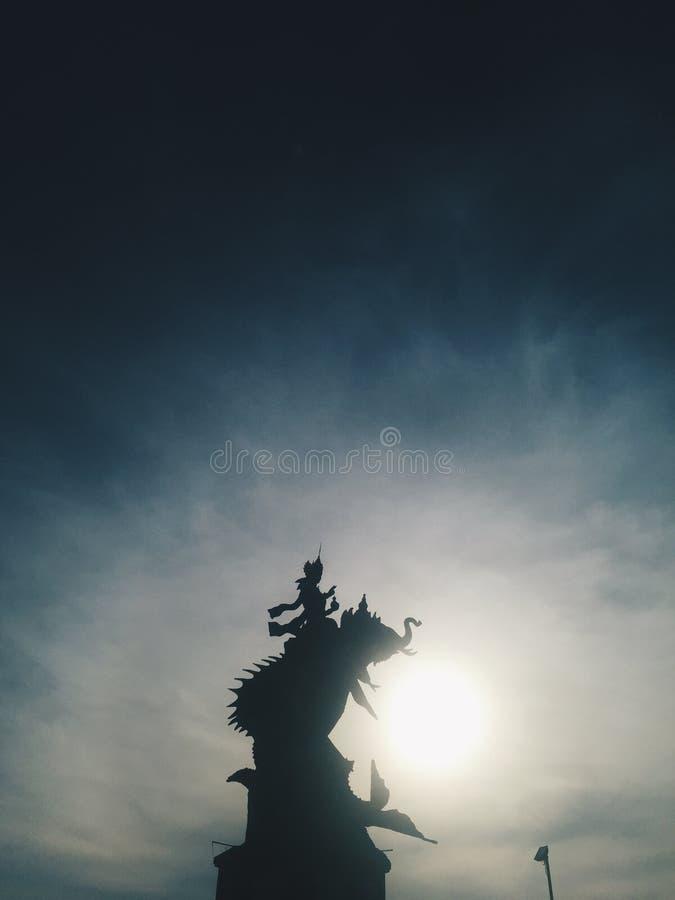 Silhouet van Indonesisch standbeeld bij blauwe hemel bij achtergrond bij zonsondergang stock afbeelding