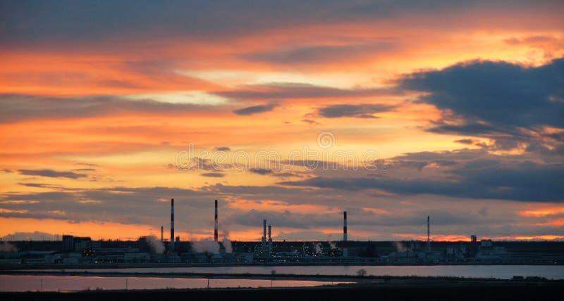 Silhouet van industriële fabriek bij zonsondergangspiegel in water stock fotografie