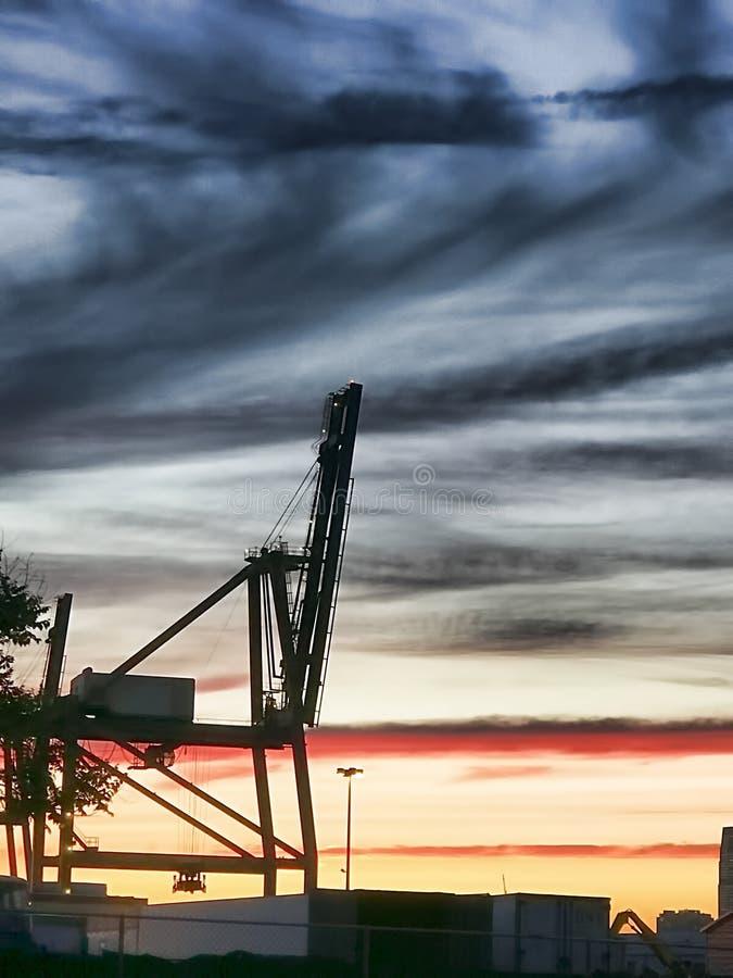 Silhouet van industriële kraan tegen avondhemel royalty-vrije stock foto