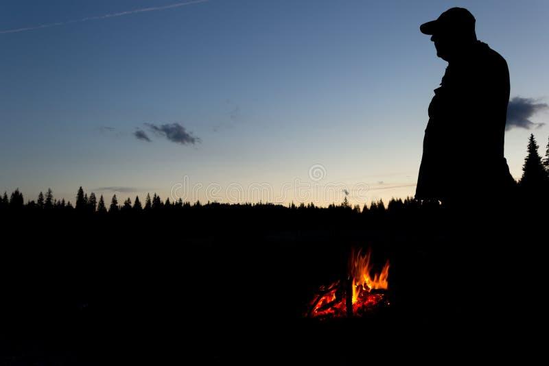 Silhouet van jager met kampvuur stock foto's
