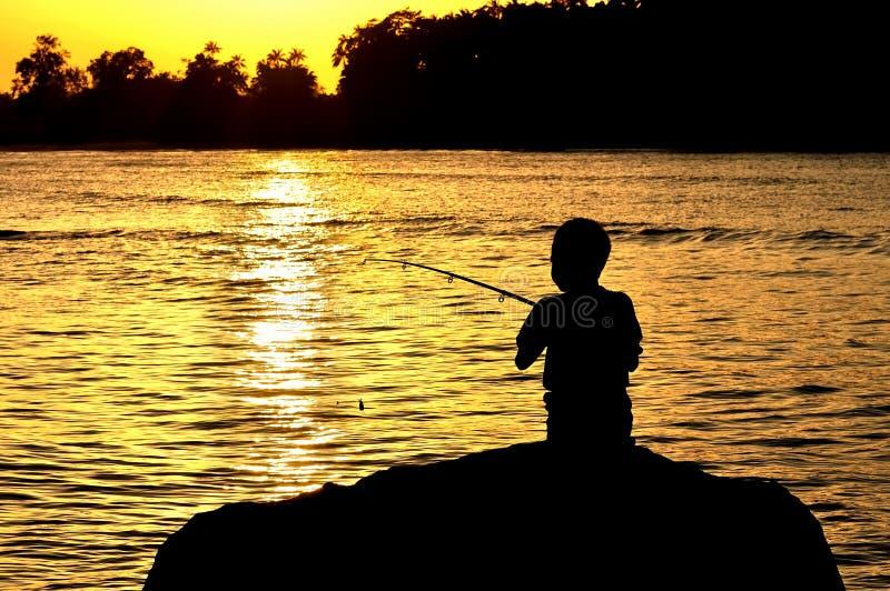 Silhouet van jong geitje visserij stock foto