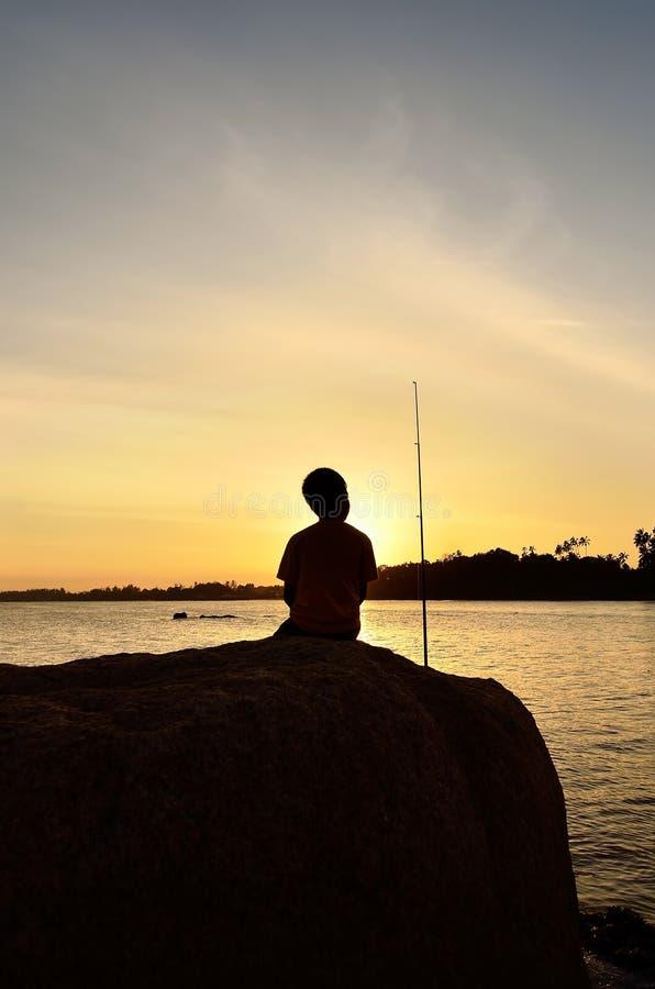 Silhouet van jong geitje visserij royalty-vrije stock foto